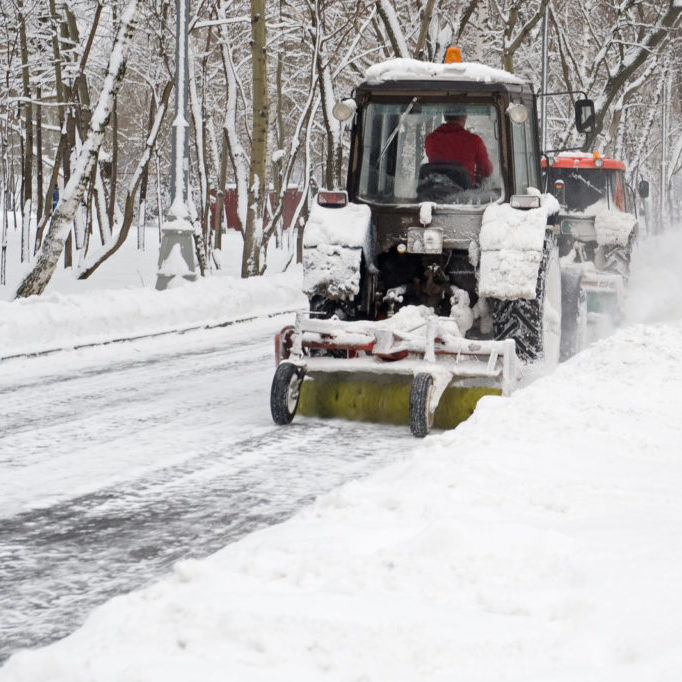 worker driving the snow blower
